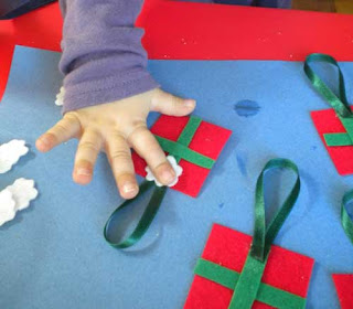 toddler gluing bow on hand made Christmas ornament