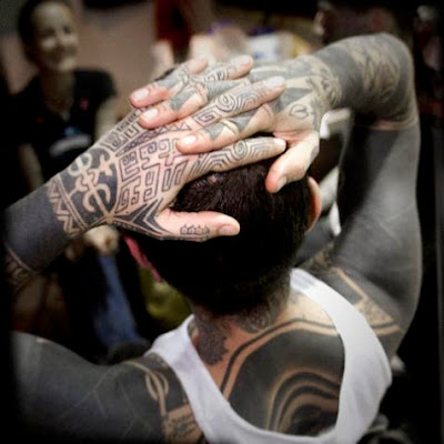 Maori black body tattoo on a white boy's body.
