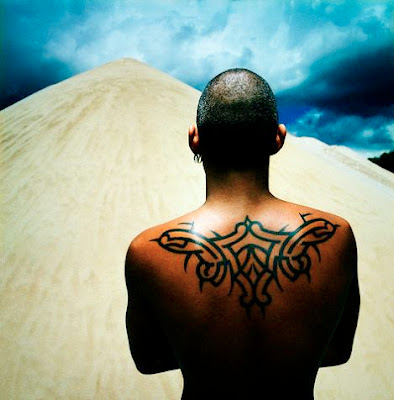 A Latino man with back tribal tattoo