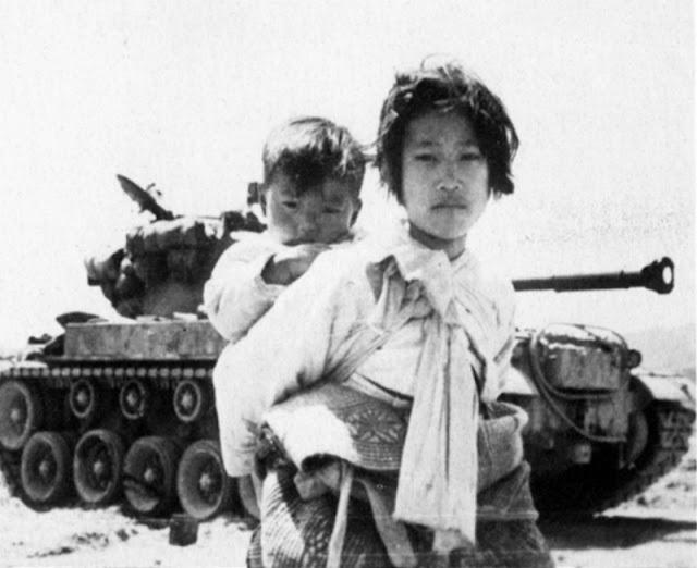 Refugiada coreana con niño y tanque durante la Guerra de Corea