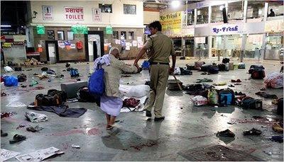 Seorang Polisi India menggandeng bapak tua di lokasi penembakan