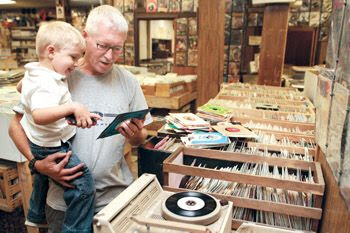Staff photo/Josh White - Gail Andersen and his grandson, Gavin, check the condition of several old 45's during a Friday afternoon trip to Kanesville Kollectables. Andersen has been sifting through records at the store since the early 1980's.