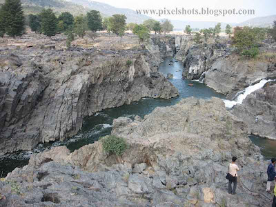 landscape of rocks and river flowing between huge rocks photograph from hogenekkal tourism spot of south india