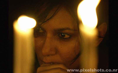 public community prayers in candle light after the mumbai terrorist attacks,photograph of woman crying while praying