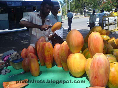 papaya fruits photographed from street side papaya seller in kerala,kappakka, kappayka, pappaya friut medicinal uses, slice ripe pappaya fruits, street fruit merchants, skin peeled ripe red pappaya fruits, photograph of fruits from fruit sellers in kerala,fruits photography