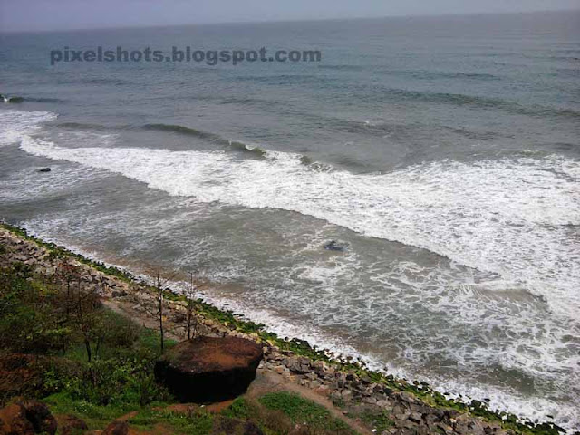 white sea waves splashing the beach rocks photographed from helipad mountain cliff of varkala