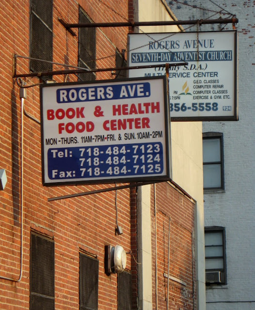Two signs in Brooklyn. One for a seventh day adventist church and one for a bookstore