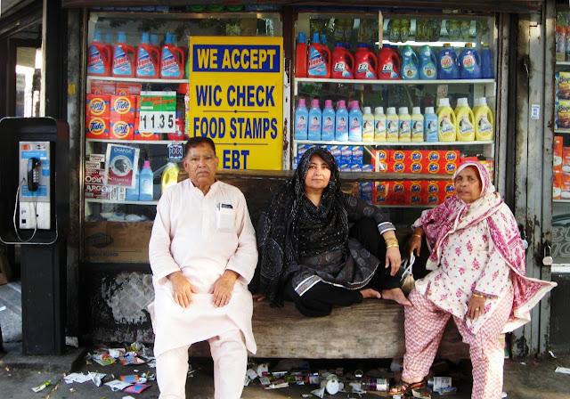 Grunge shot of people posing at corner store with garbage