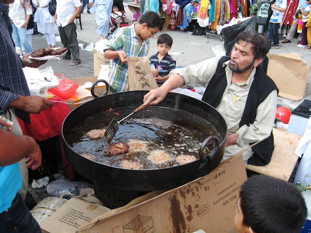 Man cooking meat on the street in huge pan with oil