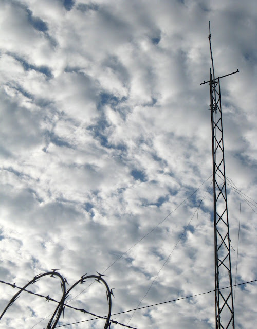 Clouds with antenna towser and razor wire in silhouette