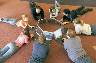 Children sitting in a circle on the floor using computers.