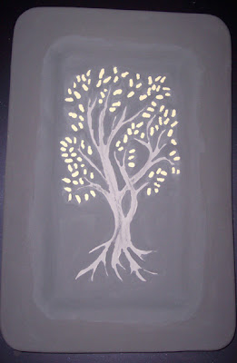 Tree design with gold leaves painted in glaze on ceramic platter.