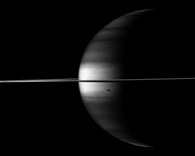 The Cassini spacecraft's camera looks in near-infrared light at a dramatic view of Saturn, its ringplane and the shadows of a couple of its moons.