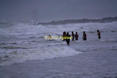 People enjoying the surf at Vagator Beach in Goa