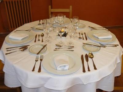 Mesa puesta con mantel, platos, cubiertos, copas y servilletas