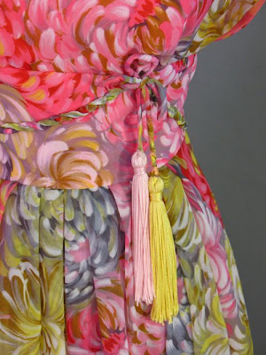 Tassels hang from a bow at the waist of this 1960s silk evening gown by