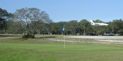Jet landing at Spruce Creek Fly-in, seen from hole 9 of the Spruce Creek Country Club