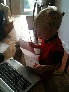 Simon reading a birthday card and talking to dad on skype