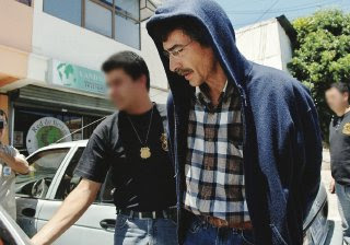 Attorney Esteban Soler is arrested by an unidentified police officer at his home in San Jose, Costa Rica, February 4, 2008. Solera was arrested on suspicion of participating in an adoption scheme that paid poor mothers for giving up their babies.