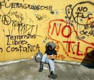 A demonstrator sits in front of a wall painted with anti-government slogans during a protest in San Jose February 26, 2007 against the proposed free trade pact between Costa Rica and the U.S. (Photo: REUTERS/Juan Carlos Ulate)
