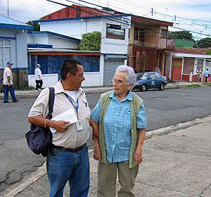 Postal carrier Roberto Montero Reyes, a 27-year veteran, chats with a resident of Tibas, Costa Rica. Delivering mail means deciphering addresses that read like treasure-hunt clues. (Maria Dickerson/L.A Times)