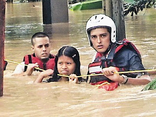 A Costa Rican Red Cross member helps evacuate two residents stranded in the flooded Sixaola area. (Photo:Carlos Rodriguez/Al Dia Newspaper)