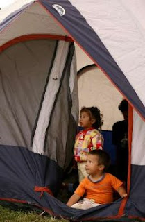 Children stand in a tent at a field used as a temporary refuge for earthquake survivors in Laguna of Fraijanes, 65 km (40 miles) north of San Jose, January 12, 2009. REUTERS/Juan Carlos Ulate (COSTA RICA)