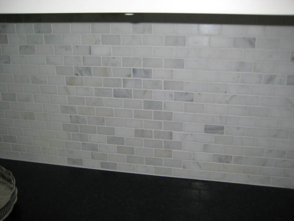 white kitchen black countertops marble tile backsplash glass shelves