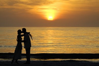 couple kissing in front of sunset