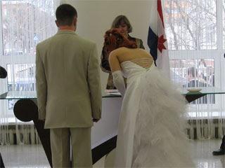 Жених и невеста расписываются в ЗАГСе