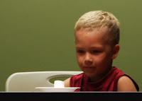 Menino olha fixamente para uma guloseima no prato