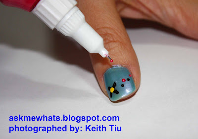 Using a pink nail art pen, create dots just below the black dots,