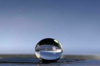 A drop of water balances perfectly on a plastic surface invented by researchers at Ohio State University. The surface is covered with microscopic fibers, and can be made to attract or repel water. The surface shown here is water repellant, so the drop can't spread out along the surface; instead, it retains its spherical shape. Photo by Jo McCulty, courtesy of Ohio State University.