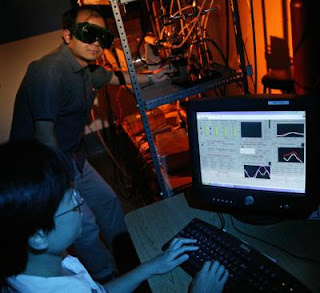 Caption: Graduate students Ganhua Lu (in back) and Ming Liu operate the equipment called a mini-arc plasma reactor