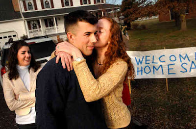 With his sister Molly (left) looking on, 1st. Lt. Sam Chamberlain receives a kiss from his wife, Gretchen, during a visit to his parents' home in Stafford County. Chamberlain recently completed a tour of duty in Iraq. Photo by FLS Bob Martin