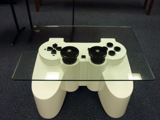 Controle gigante de PlayStation como mesa de café