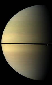 The moon Rhea, at far right, is dwarfed by Saturn. The shadow of another moon, Tethys, dots the disk at far left