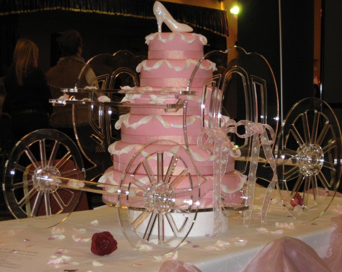 Six tier Cinderella 39s carriage wedding cake in pink with glass carriage and