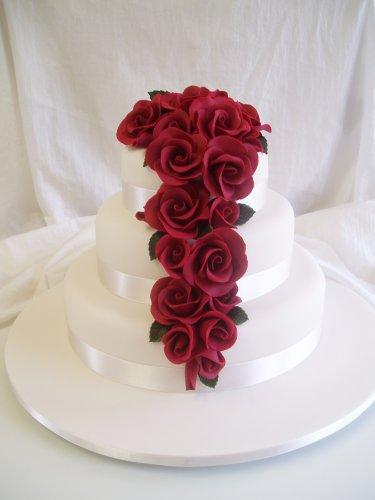 Gorgeous white wedding cake with elegant and romantic draping and blood red