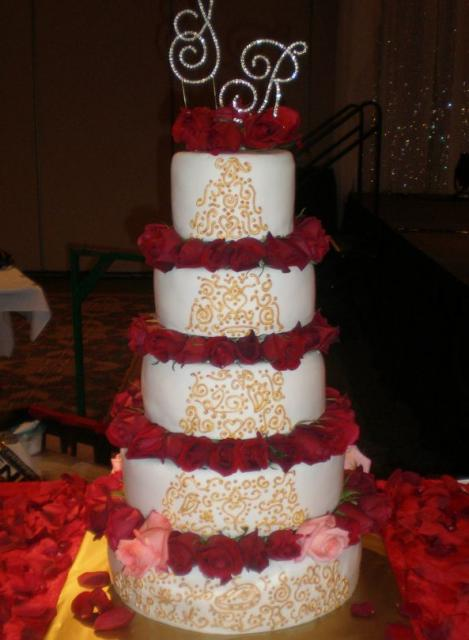 Simple five tier wedding cake with gold decoration and plenty of lush red