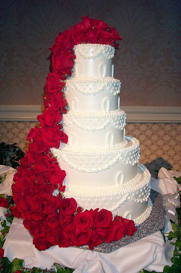 Classic and elegant wedding cake with red ribbons and red roses