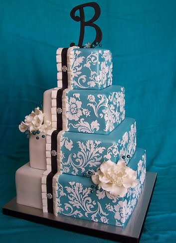 Blue damask wedding cake over thress square tiers with orange roses