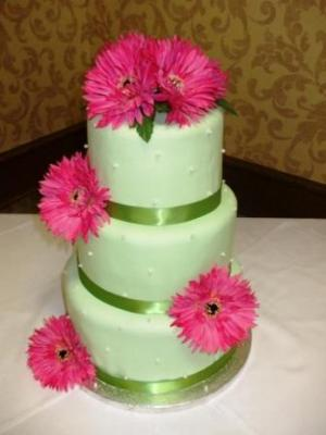 Four tier green round wedding cake with bright pink flowers