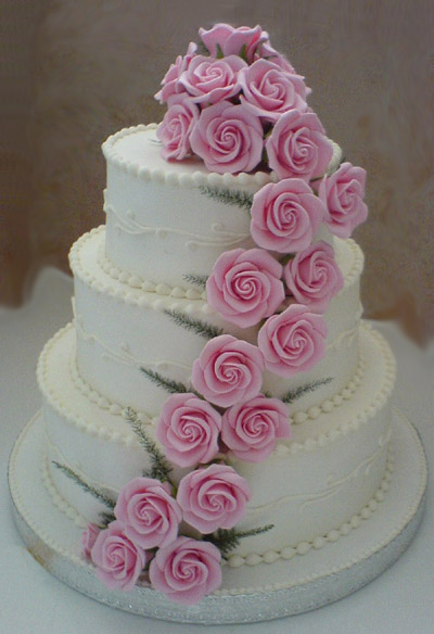 Classic three tier white wedding cake with light pink sugar roses cascading