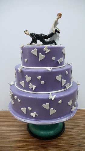 Purple wedding cake over three tiers with heart and white butterflies