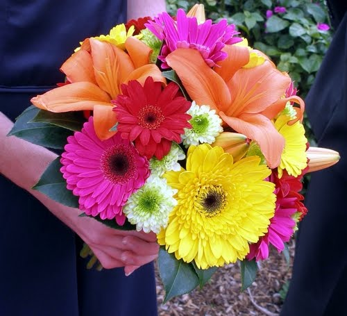 Yellow hot pink and fuchsia gerbera daisies mixed with orange lilies
