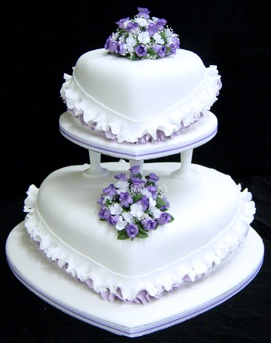 White heart shaped wedding cake with purple trimming and small purple and