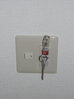 【照片:電燈開關。把鑰匙棒插進去就會打開電燈的電源了。】