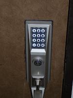 【照片:門外的電子鎖、門鎖和下壓開門式手把】