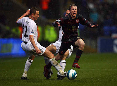 Matt Taylor and Kevin Davies of Bolton attempt to stop Alex Hleb of Arsenal.